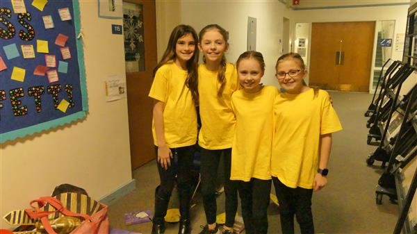 Four girls in yellow shirts